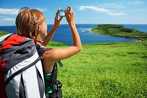Young woman with backpack taking photo of a great landscape